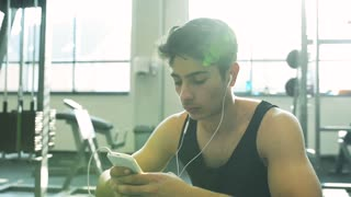 Hispanic fitness man in gym resting, holding smart phone, earphones in his ears listening music