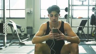 Hispanic man in gym resting, holding smart phone, listening music.