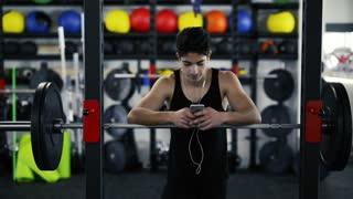 Hispanic man in gym resting, holding smart phone,listening music