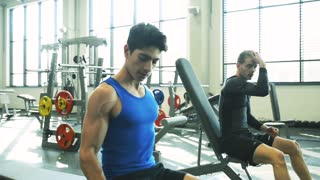 Hispanic man with his friend in gym working out with weights