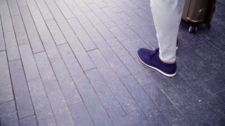Legs of businessman with suitcase walking on a pavement on the street. Copy space. Slow motion.