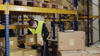 Male warehouse worker loading hand pallet truck.