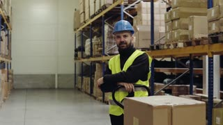 Male warehouse worker standing by pallet truck.