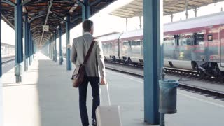 Mature businessman in a city. Man walking on the railway platform on the train station. Rear view. Slow motion