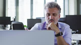 Mature businessman in the office working with laptop.