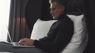 Mature businessman with laptop in a hotel room.