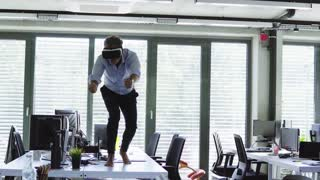 Mature businessman with VR goggles in the office.