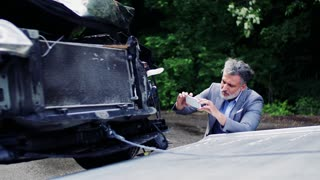 Mature man in gray suit taking pictures of a broken car after an accident.
