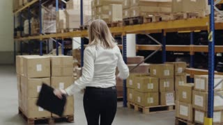 Overjoyed female worker or supervisor in a warehouse.