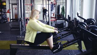 Overweight woman in gym exercising on rowing machine.