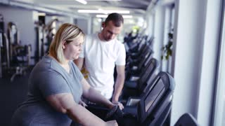 Overweight woman in gym with coach walking on treadmill.