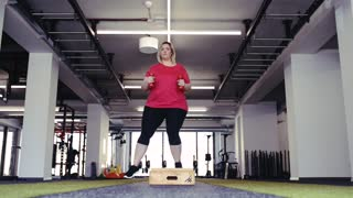Overweight woman in gym working out, doing box steps.