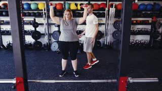 Overweight woman in modern gym working out with dumbbells.