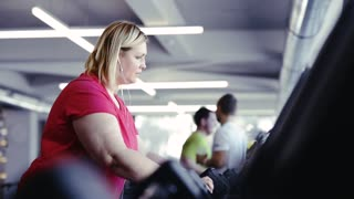 Overweight woman walking on treadmill in modern gym.
