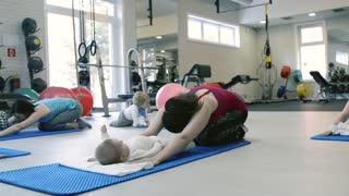 Parents exercising with babies in gym, stretching back.