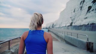Rear view of a young sporty woman runner with earphones walking outside on the beach in nature, listening to music and looking back. Copy space. Slow motion.