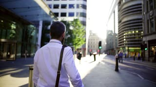 Rear view of hipster businessman walking down the street in London, looking back. Copy space. Slow motion.