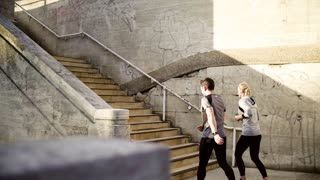 Rear view of young couple runners running up the stairs in the city. Slow motion.