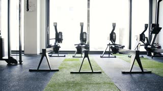 Rowing machines in empty modern gym room. Fitness center.