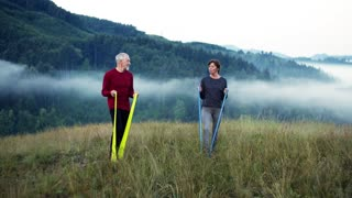 Senior couple doing exercise with resistance rubber bands on meadow in foggy morning in nature.