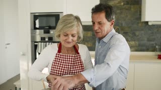 Senior couple in the kitchen cooking together, woman adding ingredients into the pot