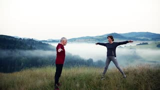 Senior couple runners stretching on meadow outdoor in foggy morning in nature, bending forward. Slow motion.