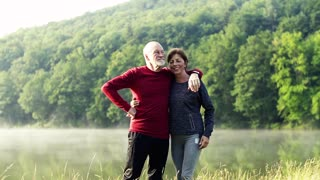 Senior couple standing by the lake outdoor in foggy morning in nature. Slow motion.