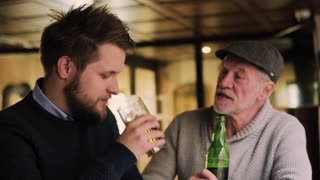 Senior father and his young hipster son drinking beer in a pub