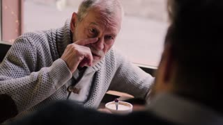 Senior father and his young son drinking coffee in a cafe