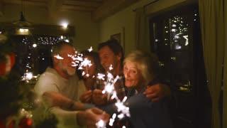 Senior friends with sparklers next to Christmas tree having fun.