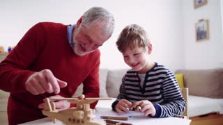 Senior grandfather with a small grandson at home drawing a helicopter. Slow motion.