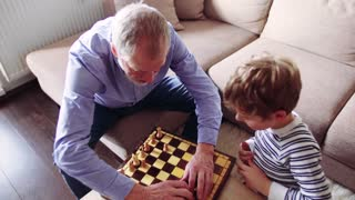 Senior grandfather with a small grandson tidying up after playing chess at home.