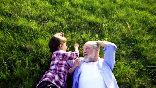 Senior grandfather with granddaughter outside in spring nature, lying on the grass and relaxing at sunset. Slow motion.