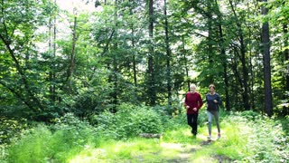 Senior happy sporty couple running in the forest outdoors in sunny nature.