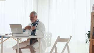 Senior male doctor working on laptop at the office desk