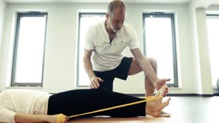 Senior male physiotherapist working with a young female patient.