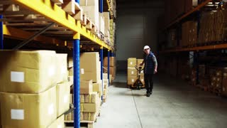 Senior male warehouse worker pulling a pallet truck with boxes.