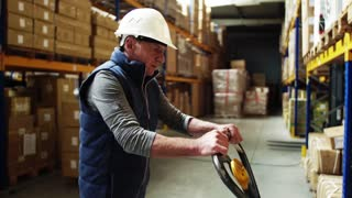 Senior male warehouse worker with a pallet truck, working. A forklift truck in the background.