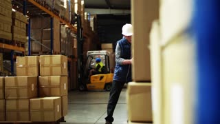 Senior male warehouse worker with white helmet loading a pallet truck with boxes. A forklift truck in the background.