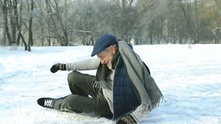 Senior man in sunny winter nature ice skating.