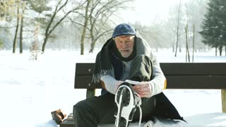 Senior man in winter clothes putting on old ice skates.