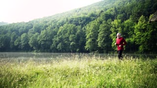 Senior man runner jogging by the lake outdoor in the morning in nature. Slow motion.