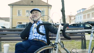 Senior man with bicycle and smart phone, making phone call