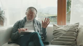Senior man with tablet relaxing at home.