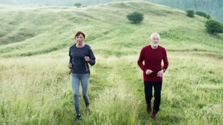 Senior sporty couple running on meadow outdoors in nature in the foggy morning.