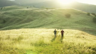 Senior sporty couple running on meadow outdoors in sunny nature at sunrise.