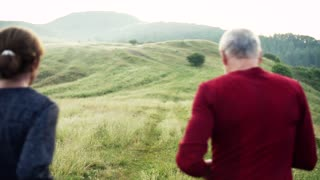 Senior sporty couple running on meadow outdoors in sunny nature in the foggy morning. Slow motion. Rear view.