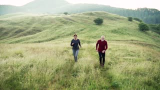 Senior sporty couple running on meadow outdoors in sunny nature in the foggy morning. Slow motion.