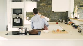 Senior woman and man in the kitchen cooking and dancing together.