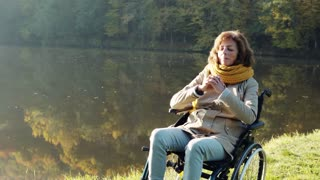 Senior woman in a wheelchair in an autumn nature. A woman praying by the lake in the early morning